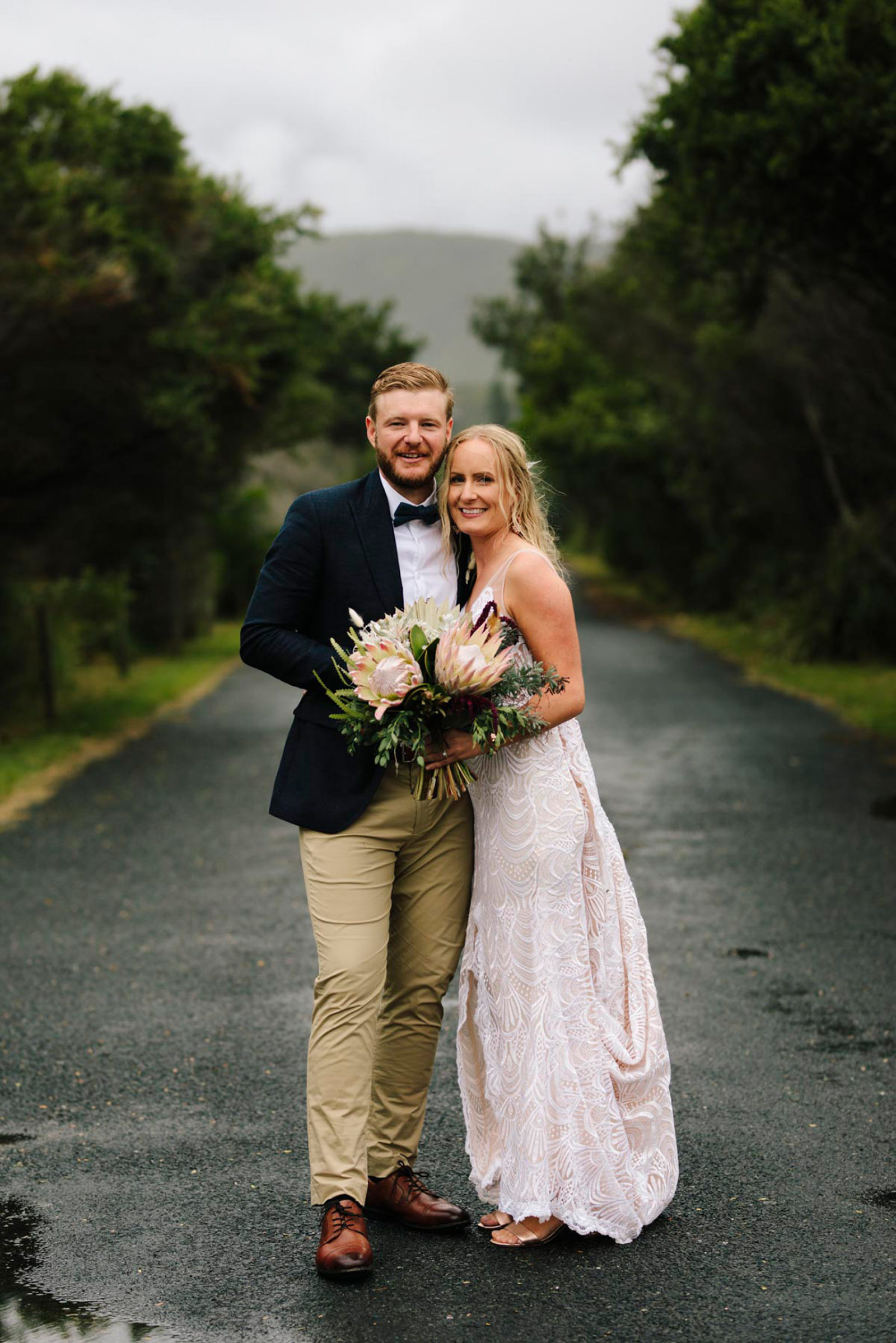 Picture of a bride and groom posing in the middle of a long road.